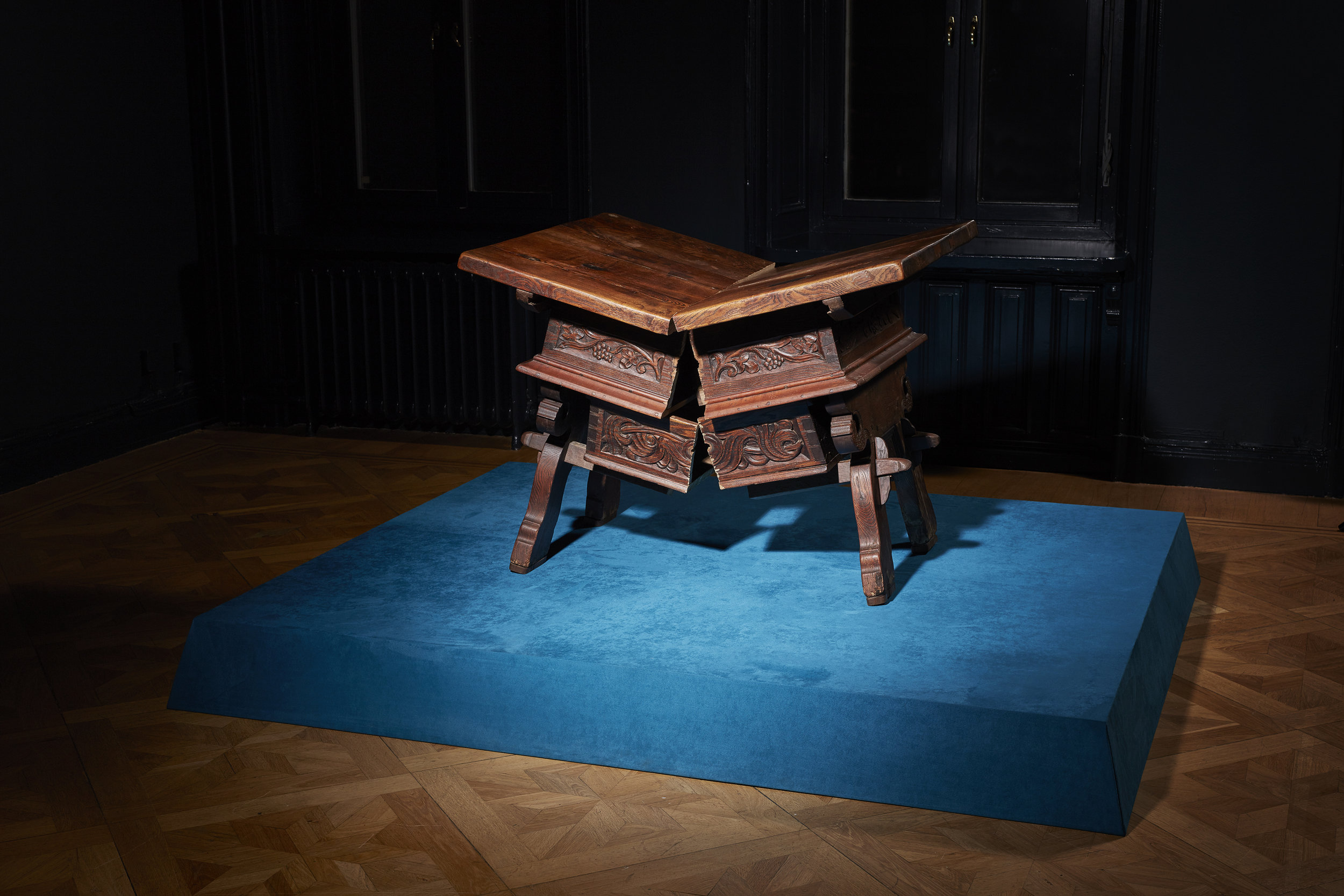 Goldin+Senneby   Banca Rotta (Central Europe, Late Baroque, oak)  2012/2017 Money-changer's table sawed in half Est. 110 x 94 x 85 cm Podium: wood, textile, 210 x 177 x 20 cm