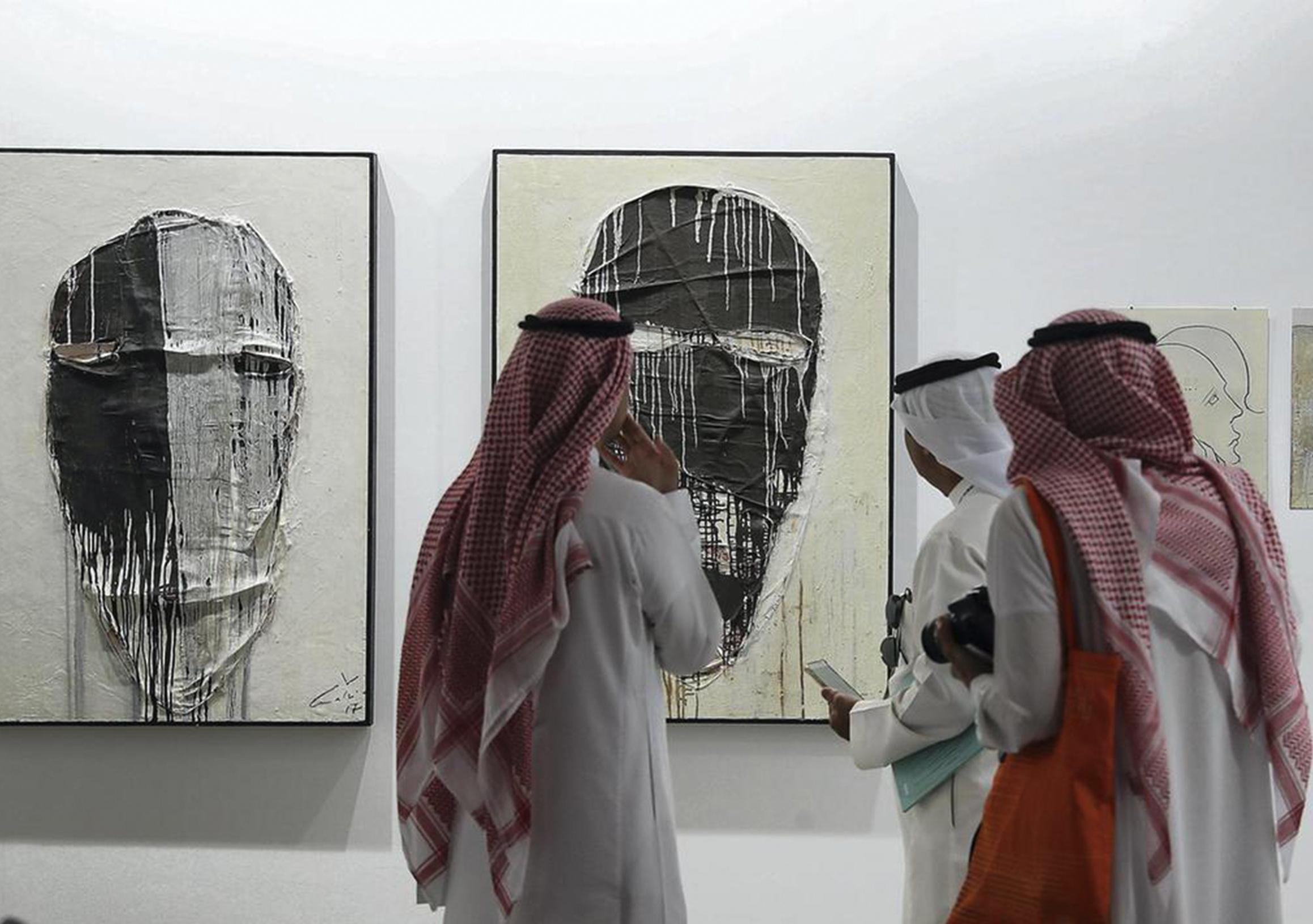 Photo: Visitors study the works on display during Art Dubai at Madinat Jumeirah. Pawan Singh / The National.