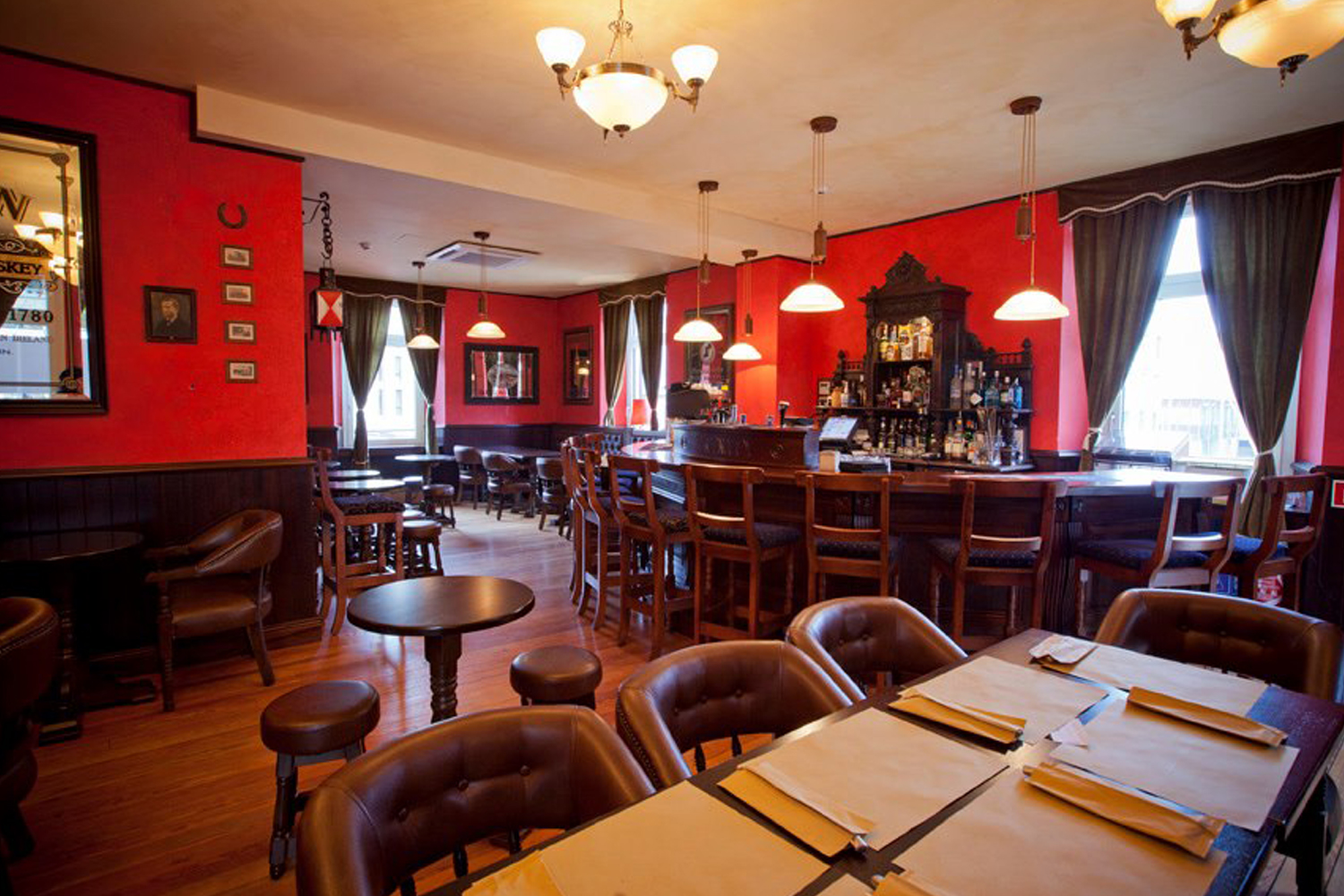 The Trinity Irish Pub design - interior design seating area with red walls and wooden furniture.