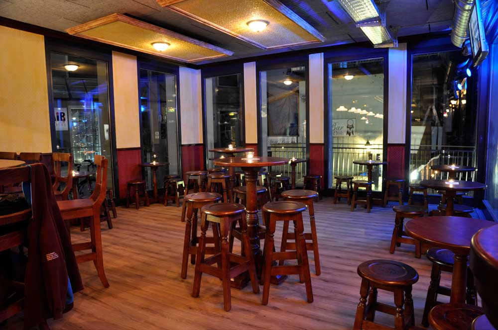 Peggy O'Neils's Irish bar design - interior seating with high wooden tables and stools