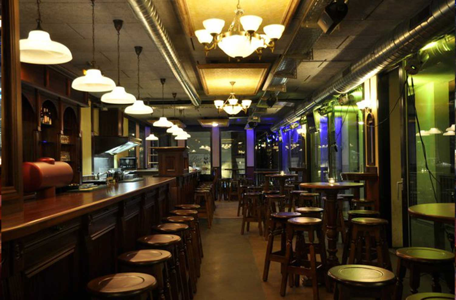 Peggy O'Neil's Irish bar design - interior wooden bar with stools lined up and high wooden tables with stools