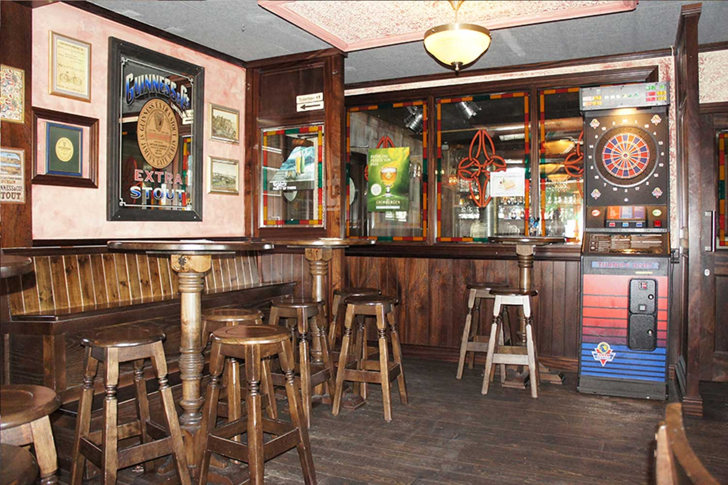 Duffy O'Toole's Irish pub design - interior view of lightwood high tables and stools and traditional Irish mirrors with Guinness logo and Celtic emblems.