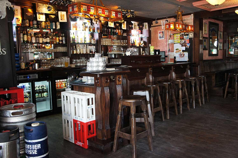 Duffy O'Toole's Irish pub design - interior view of dark wood bar, plastic pallets and kegs piled up at bar.