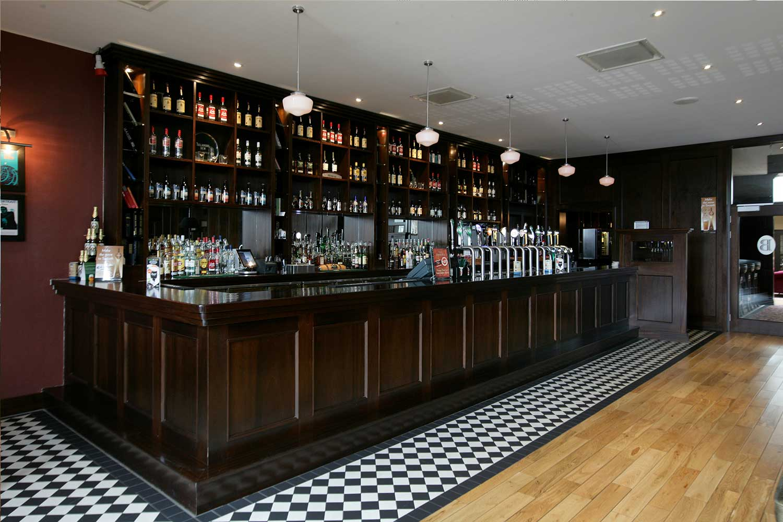 Bewley's hotel bar design - dark wood bar designed by Guinness approved designers