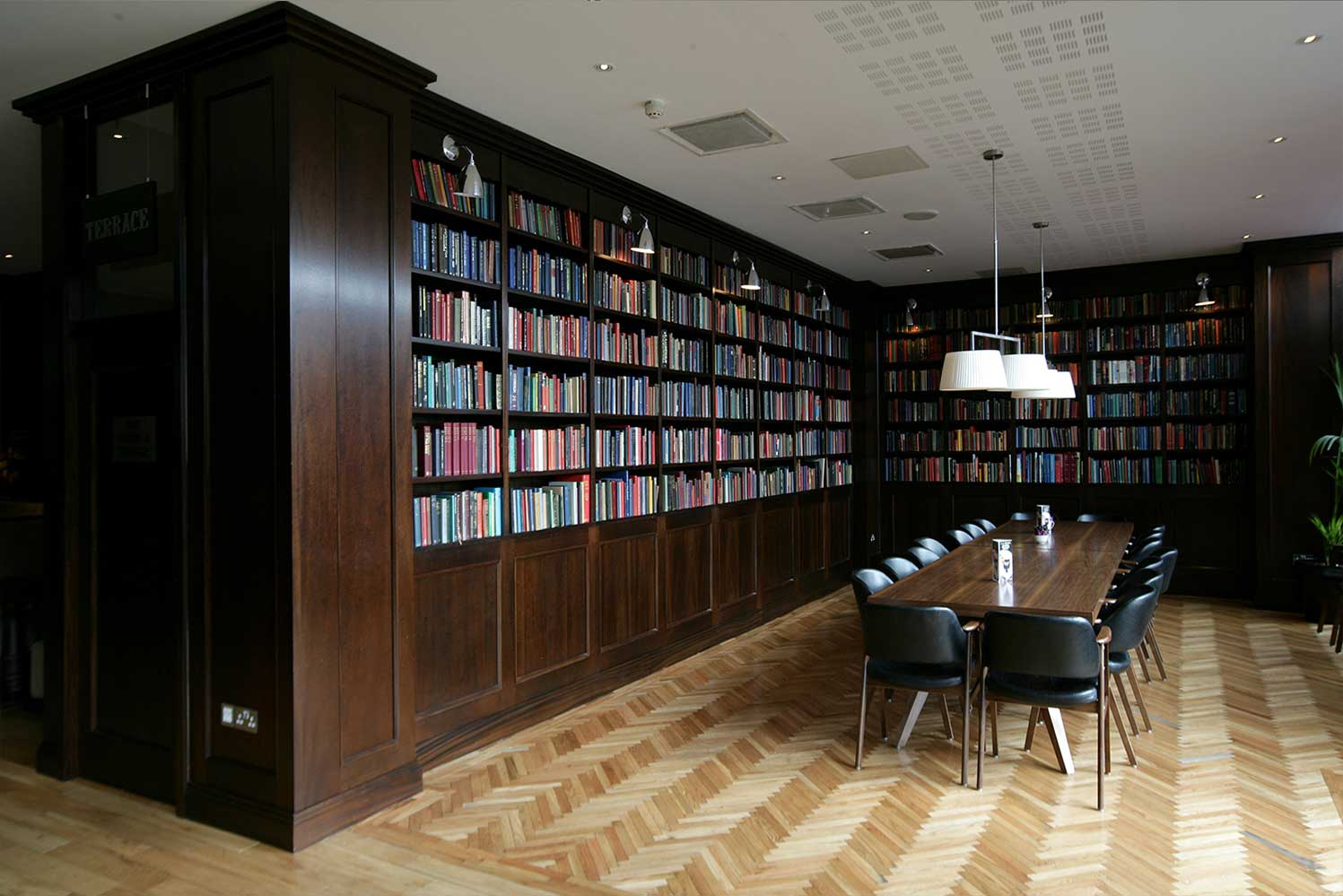 Bewley's hotel bar design - interior dining room with dark wood bookcase and long dining table