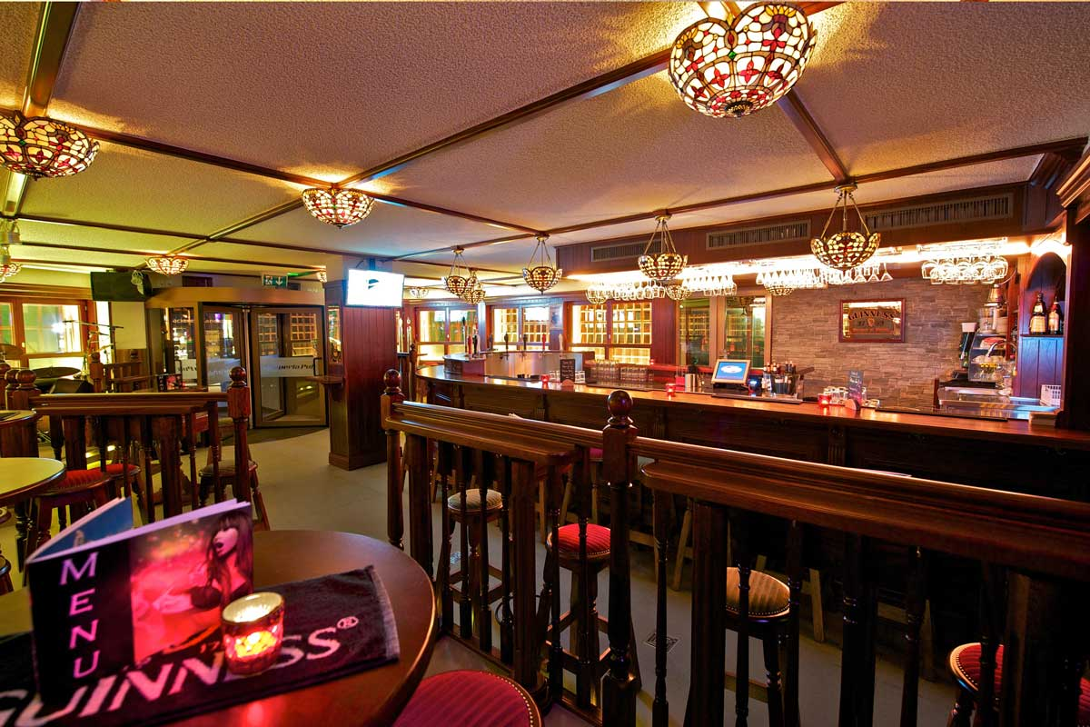 Papperla authentic Irish pub design, interior view of wooden high tables and stool seating