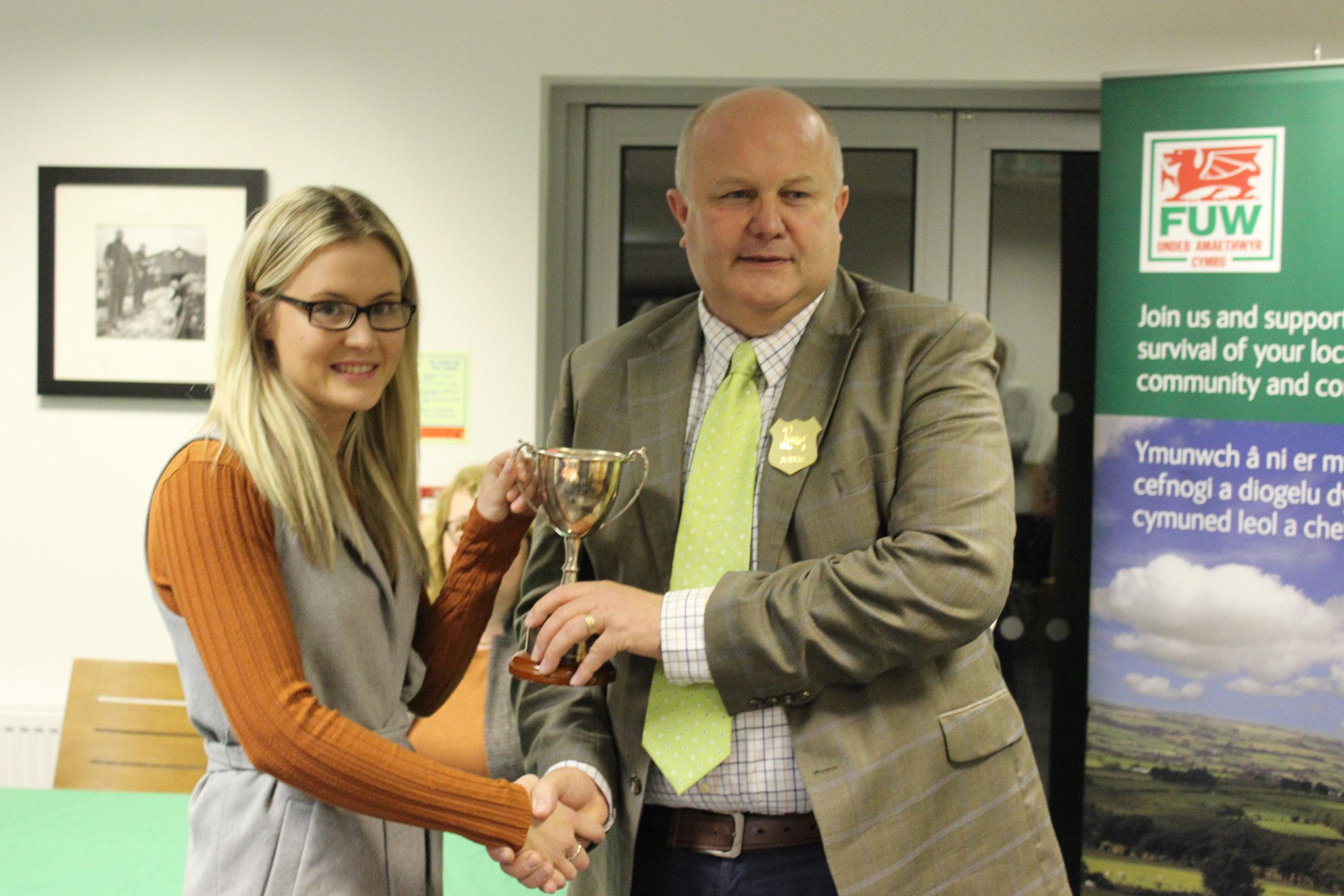 Laura Watson, Llanbadarn Fynydd YFC being presented with the Owen Duggan Memorial Cup for Best Individual by Judge Stuart Anthony.