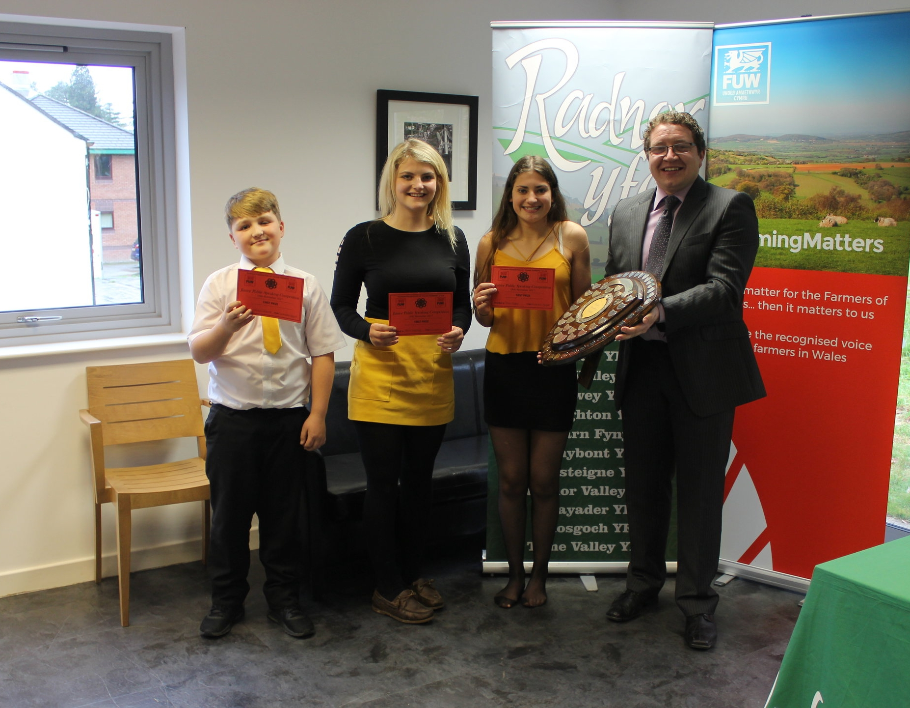 William Goodwin Edwards, Annie Fairclough and Rhian Hughes, Llanbadarn Fynydd YFC with judge Hefin Jones winning the Junior Public Speaking shield.