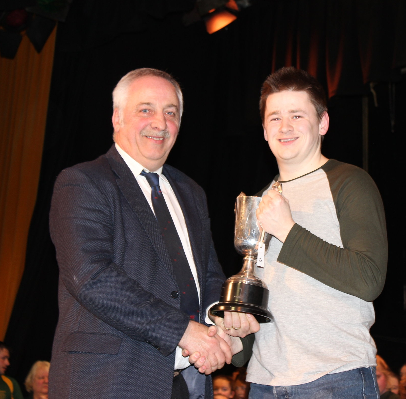 Tom Protheroe, Rhosgoch YFC being presented with the 'Estyn Meredith MBE Perpetual Trophy' for best sketch by David Powell, FUW