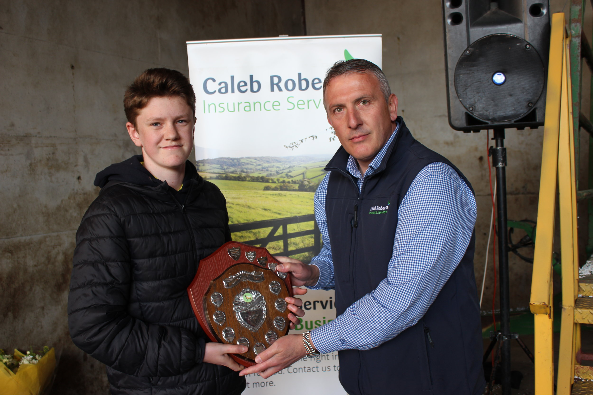 William Davies, Aberedw YFC - HM Bennett LTD Shield for Fat Lamb Judging being presented by Hugh Campbell, Caleb Roberts.