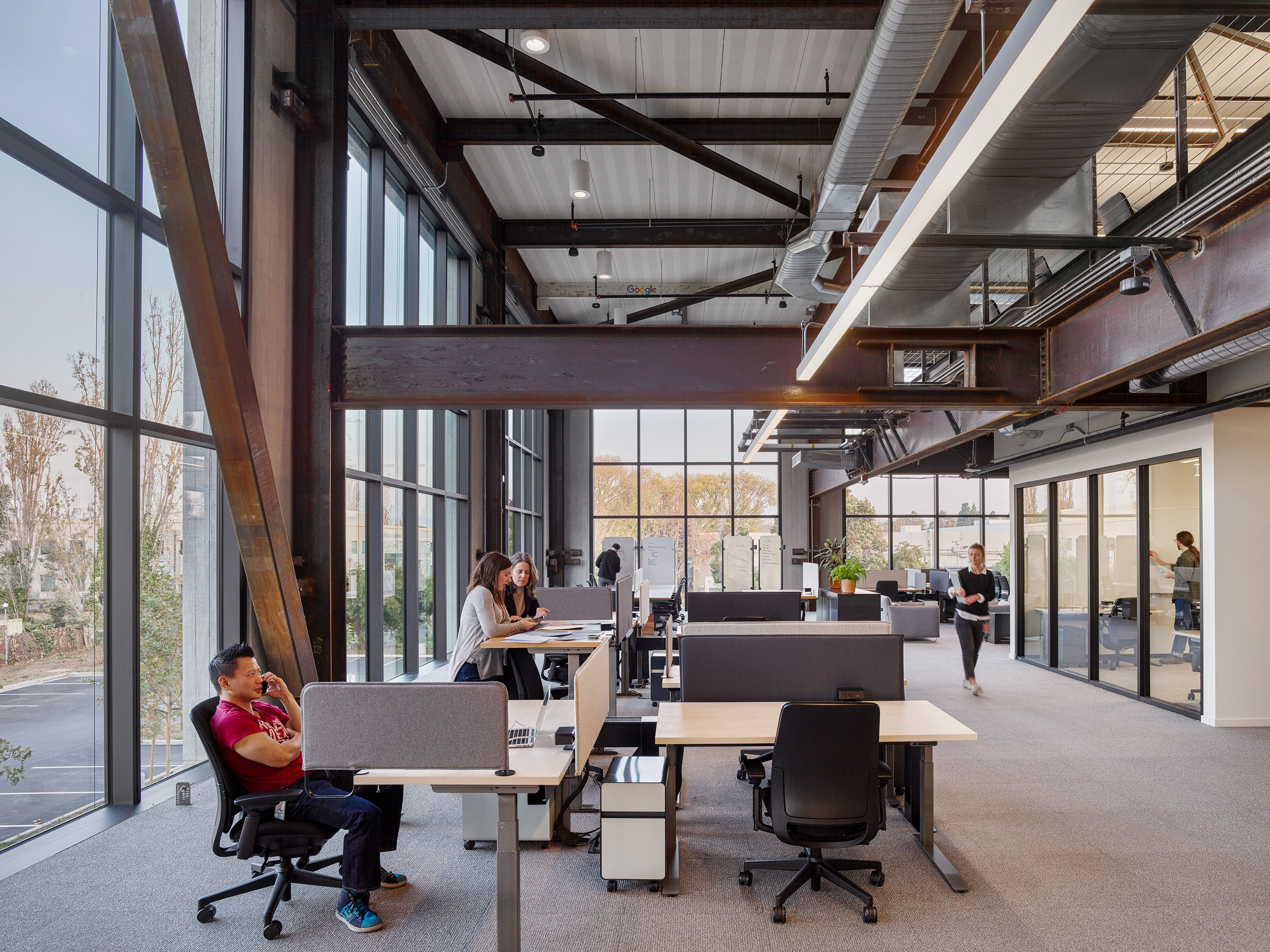 The perimeter of the building features double-height open plan workspace. Enclosed workspaces for smaller teams are below the mezzanine.