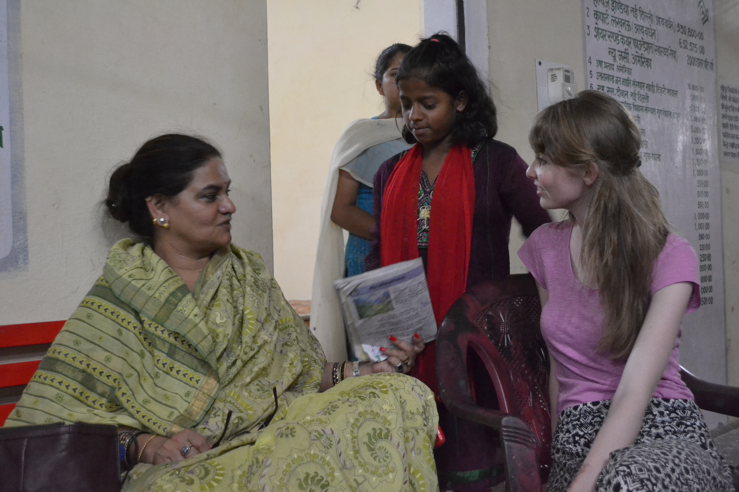 Rachna assists a girl in an orphanage to translate the national anthem from English to Hindi.