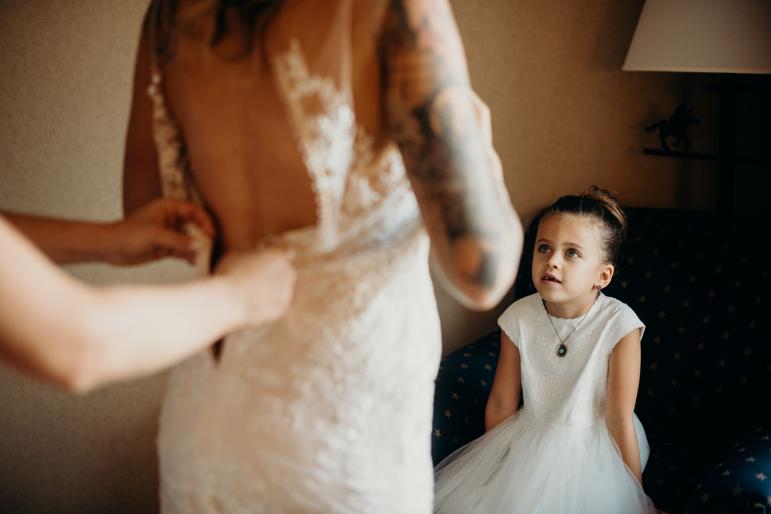 Flower girl watches the bride as she gets dressed on her wedding day in Arizona.