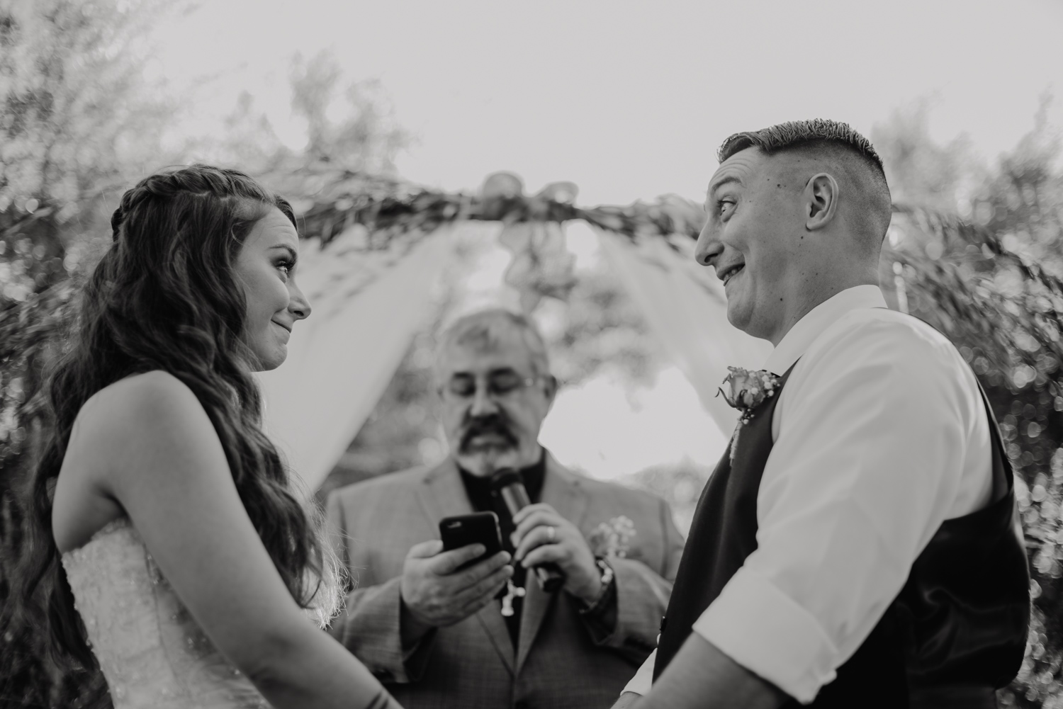 Couple makes goofy faces at each other during their reception at The Olive Mill in Queen Creek, Arizona.