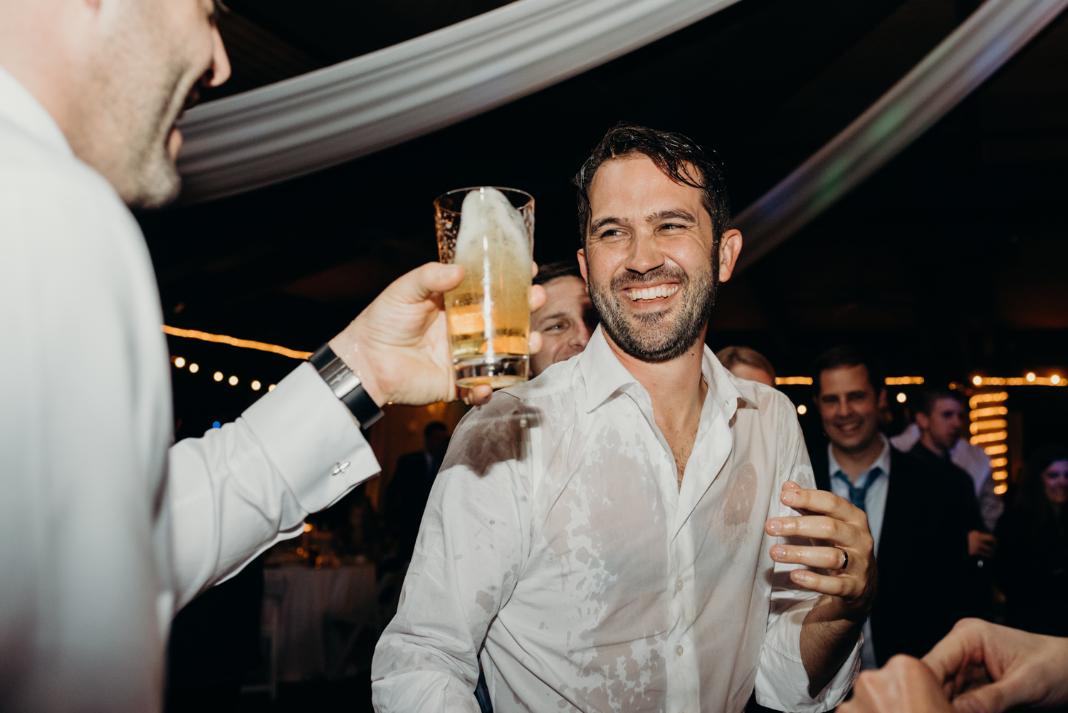 Groom laughs after he gets beer poured on him during his wedding reception at McCormick Ranch Golf Club in Scottsdale, Arizona.
