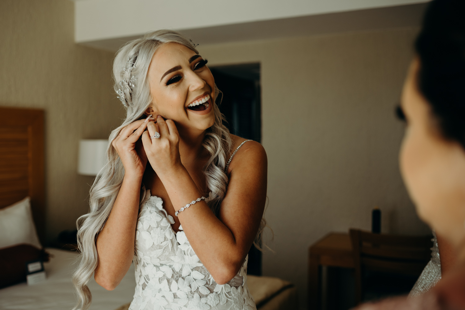 Bride putting on her jewelry for her beach wedding in Cancun, Mexico.