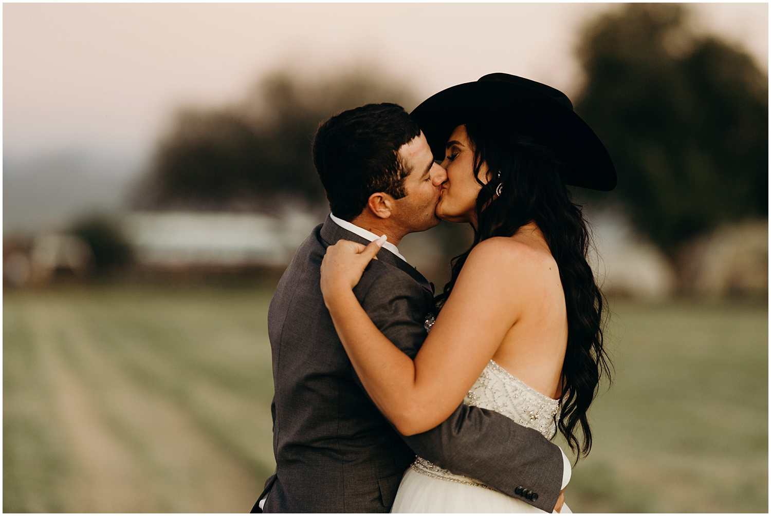 Groom puts cowboy hat on his bride and kisses her.