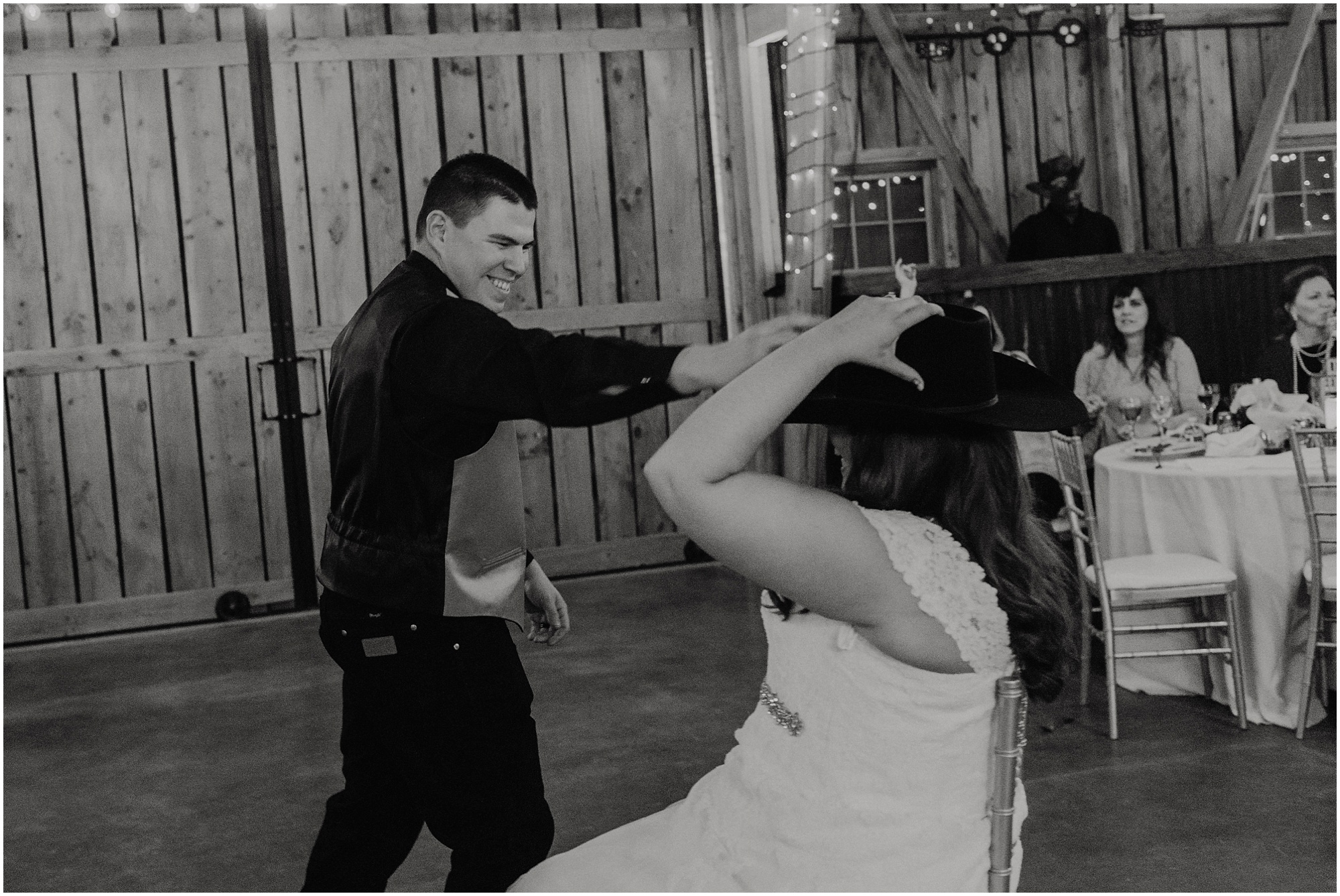 Groom places his cowboy hat on his bride during the garter toss.