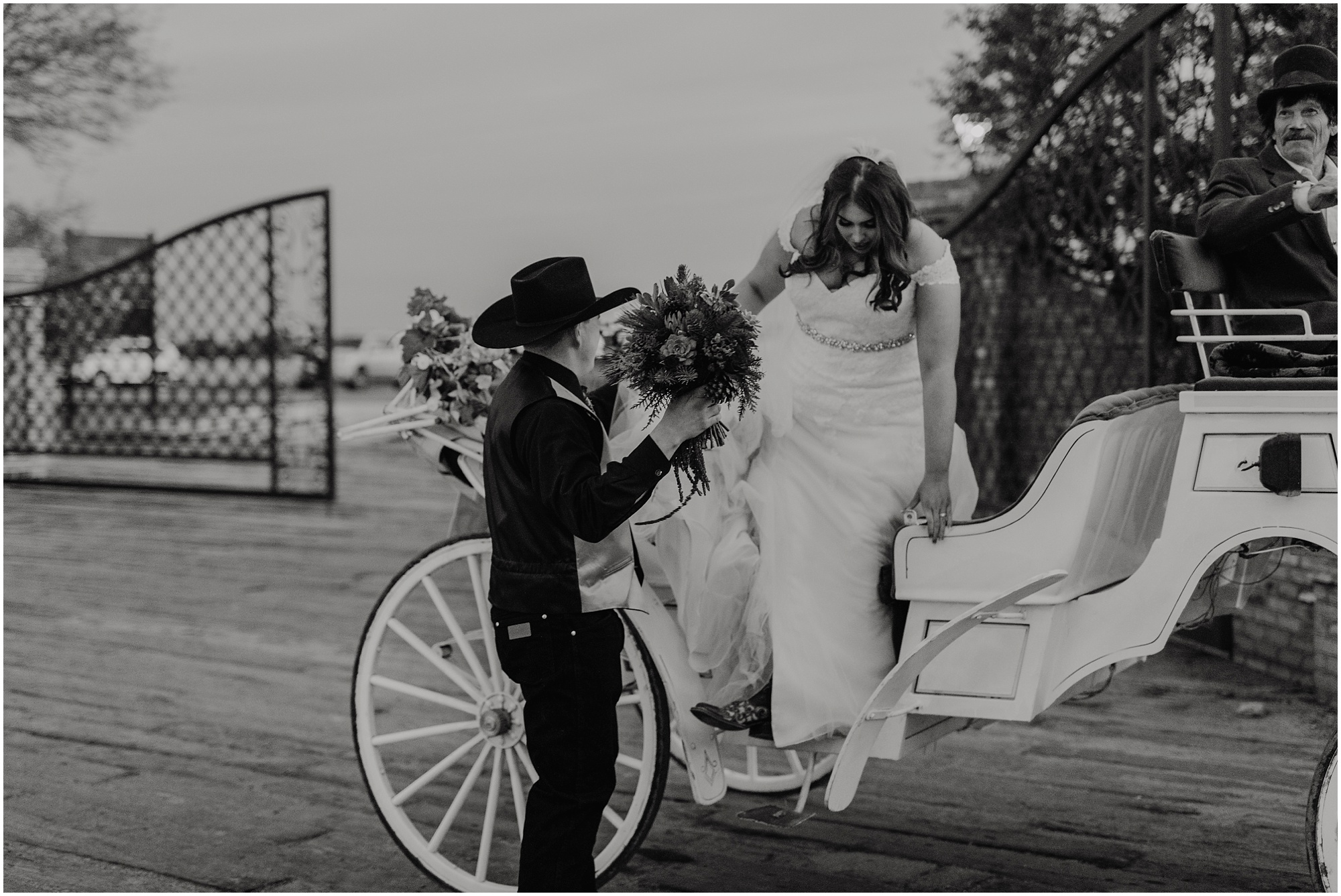 The groom helps his bride out of the horse drawn carriage after their Christmas Country Wedding.