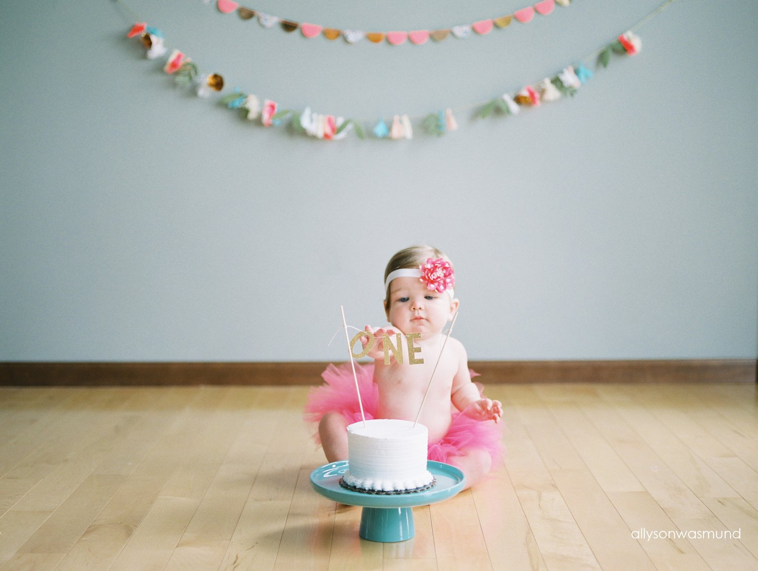 One year old girl sits behind her beautiful cake at her in-home baby milestone session in Lakeville, Minnesota.