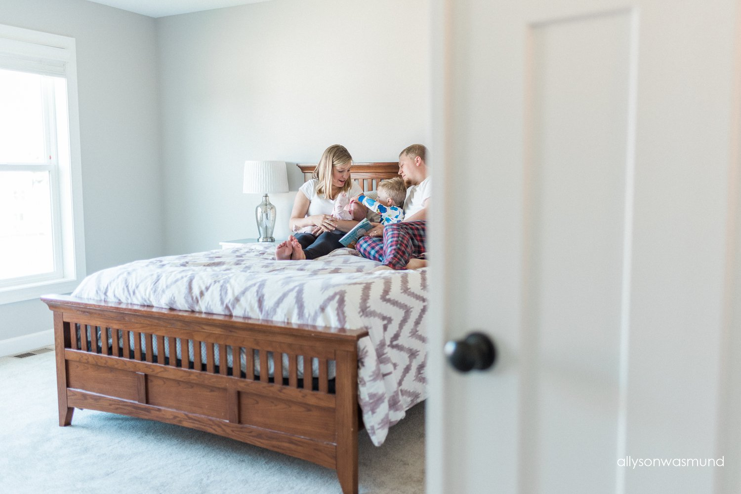 A family of four relaxes in the master bedroom of their Champlin, Minnesota home during their in-home lifestyle newborn session with Allyson Wasmund Photography.