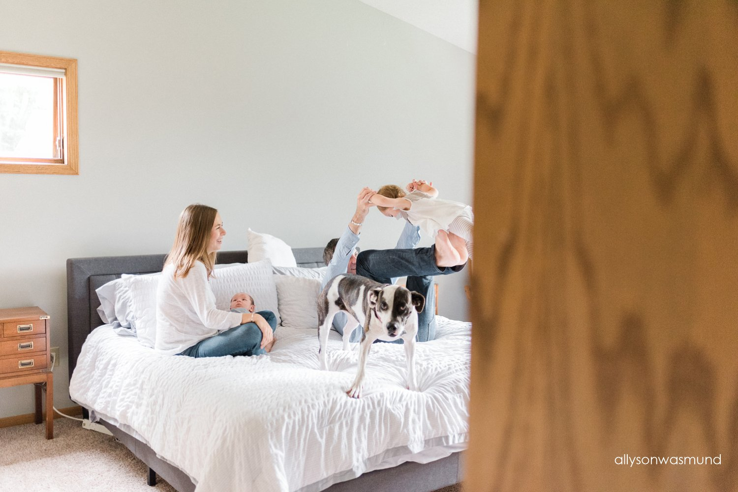 A new family of four hanging out during their Lakeville, Minnesota in home lifestyle newborn session.