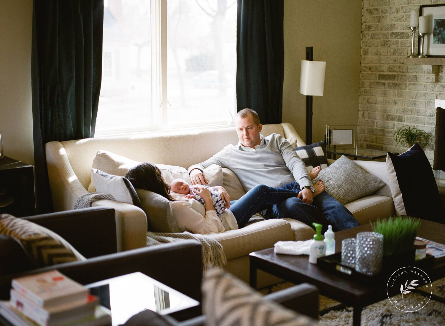 A new family of three sits on their sofa in their Minneapolis home during their lifestyle newborn session with Allyson Wasmund Photography.