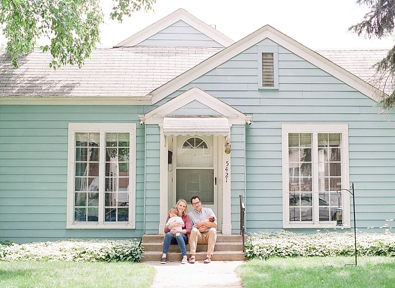 A new family of four sits on their front steps of their Minneapolis MN home after their at home newborn session with Allyson Wasmund Photography.