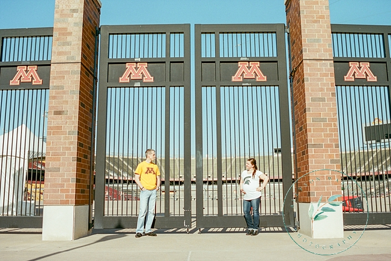 A beautiful couple stands in front of the gates of the football field on the University of Minnesota campus during their outdoor maternity session.