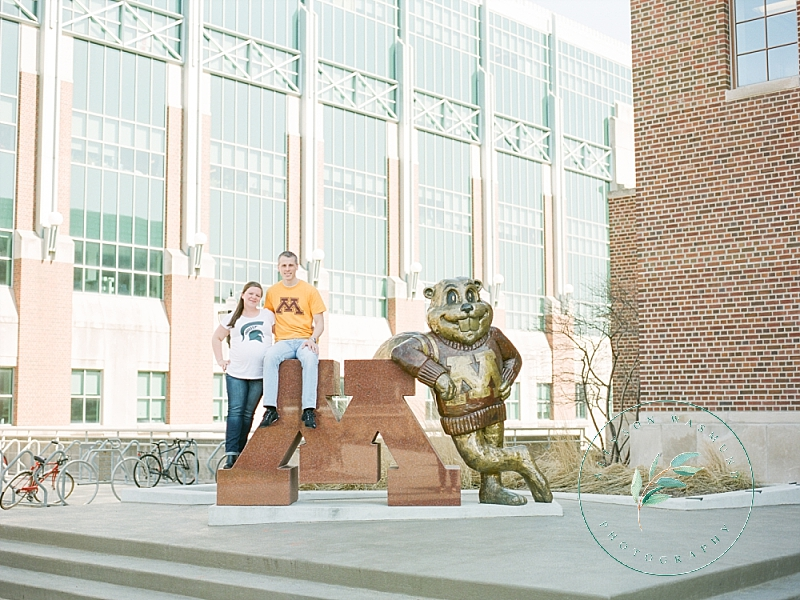 A couple that is expecting their first baby poses in front of the gopher statute on the University of Minnesota campus in Minneapolis for their outdoor maternity session.