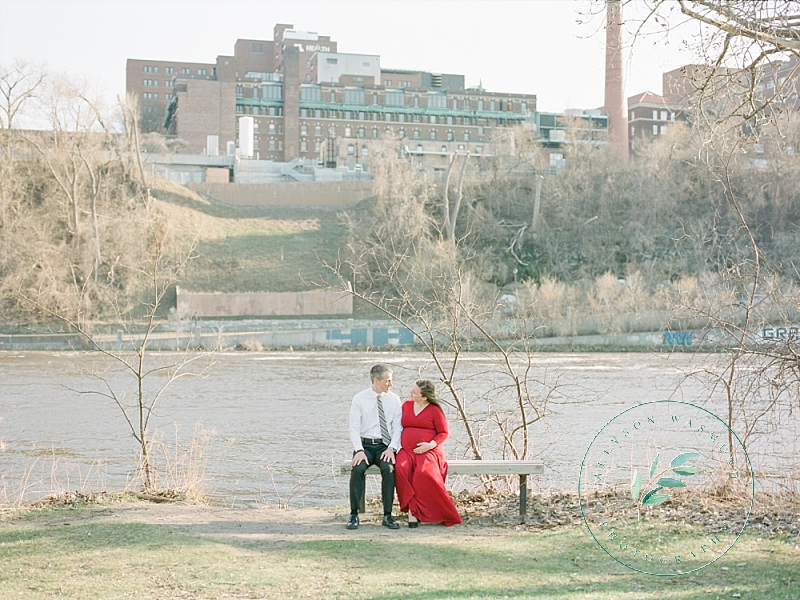 An expecting couple sits on a bench on the river bank on the University of Minnesota's campus in Minneapolis - and their hospital where their baby will be born is in the background.