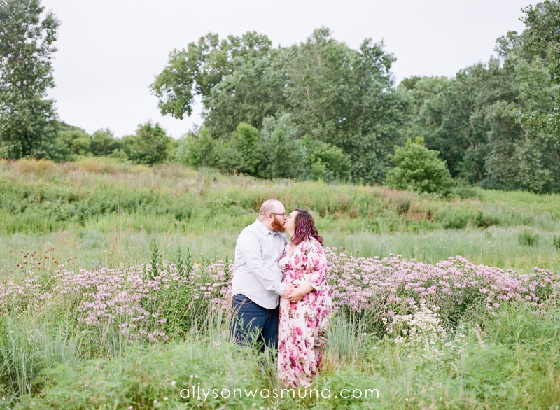 An expecting couple stands in a field of wildflowers during their outdoor maternity session in Saint Paul, Minnesota with Allyson Wasmund Photography.