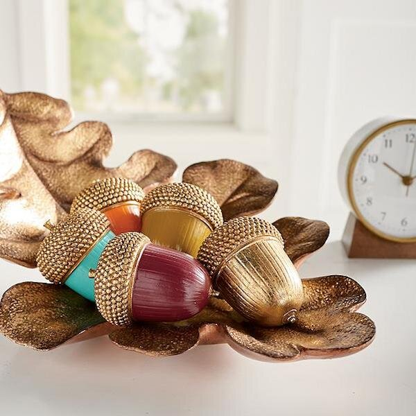 Colorful Acorns , Set of Five (Grandin Road) — $23.20   Fall doesn't have to be all oranges, yellows and browns! These decorative acorns are a modern twist on the season and would be great clustered on a console or dotting a runner on your dining room table…and their currently on sale!