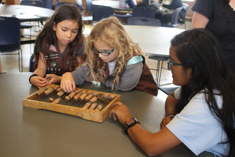 Girls learn about ancient math techniques by playing with an abacus!
