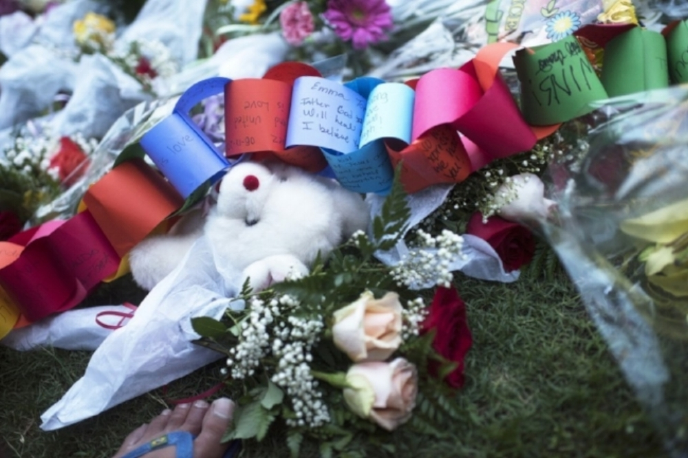 A teddy bear was among dozens of flowers left in honor of the deceased in Orlando. (Marvin Joseph/The Washington Post)