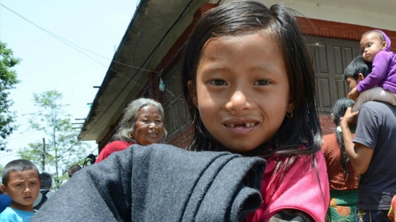 World Vision After the deadly April 25 quake in Nepal, a young survivor receives a blanket, distributed by World Vision.