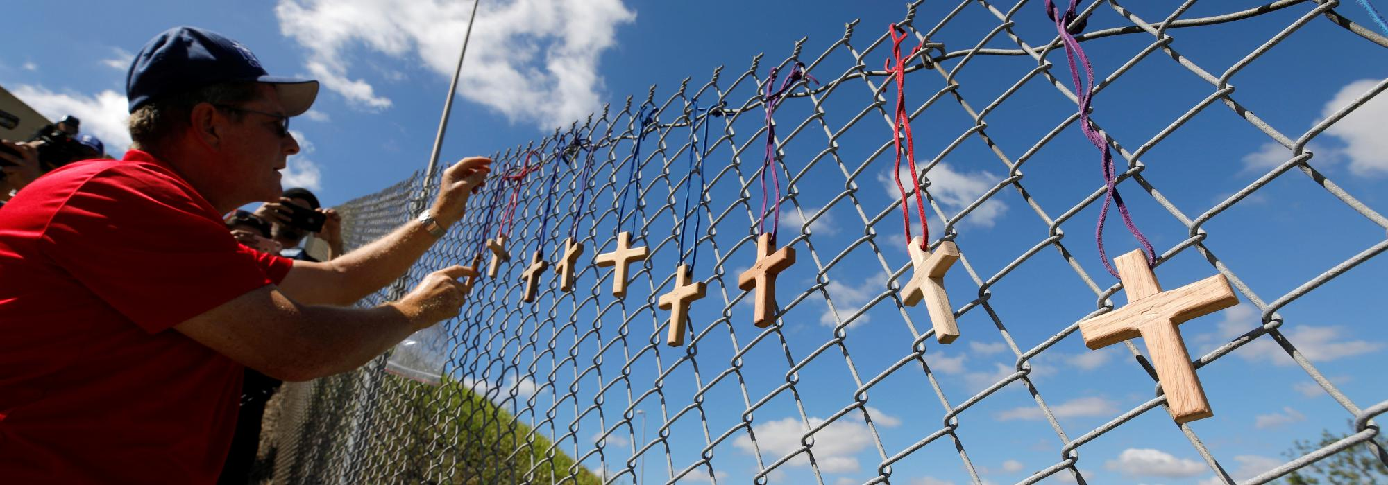 Picture above: Bob Ossler, chaplain with the Cape Coral volunteer fire department, places seventeen crosses for the victims of the shooting at Marjory Stoneman Douglas High School on a fence a short distance from the school in Parkland, Fla. Image via Reuters/Jonathan Drake