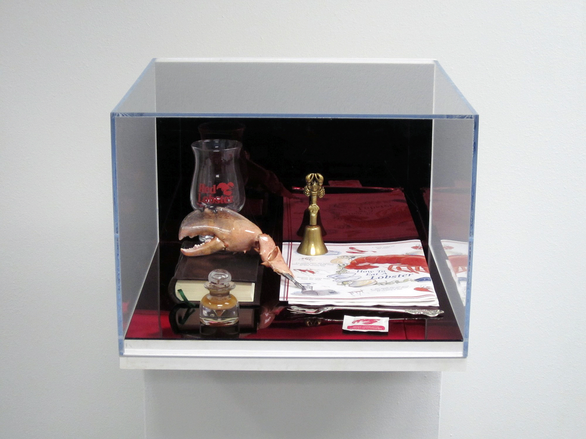 """How to Eat Lobster (Ritual)  2011 Wall mounted plexi-glass and wood vitrines, contents: red mirrored plexi-glass, """"Red Lobster"""" drinking glass, brass bell, paper placemat and napkin, leather book, moist towelette, sterling silver lobster fork, taxidermy lobster claw quill pen, homemade lobster ink with inkwell dimensions variable"""