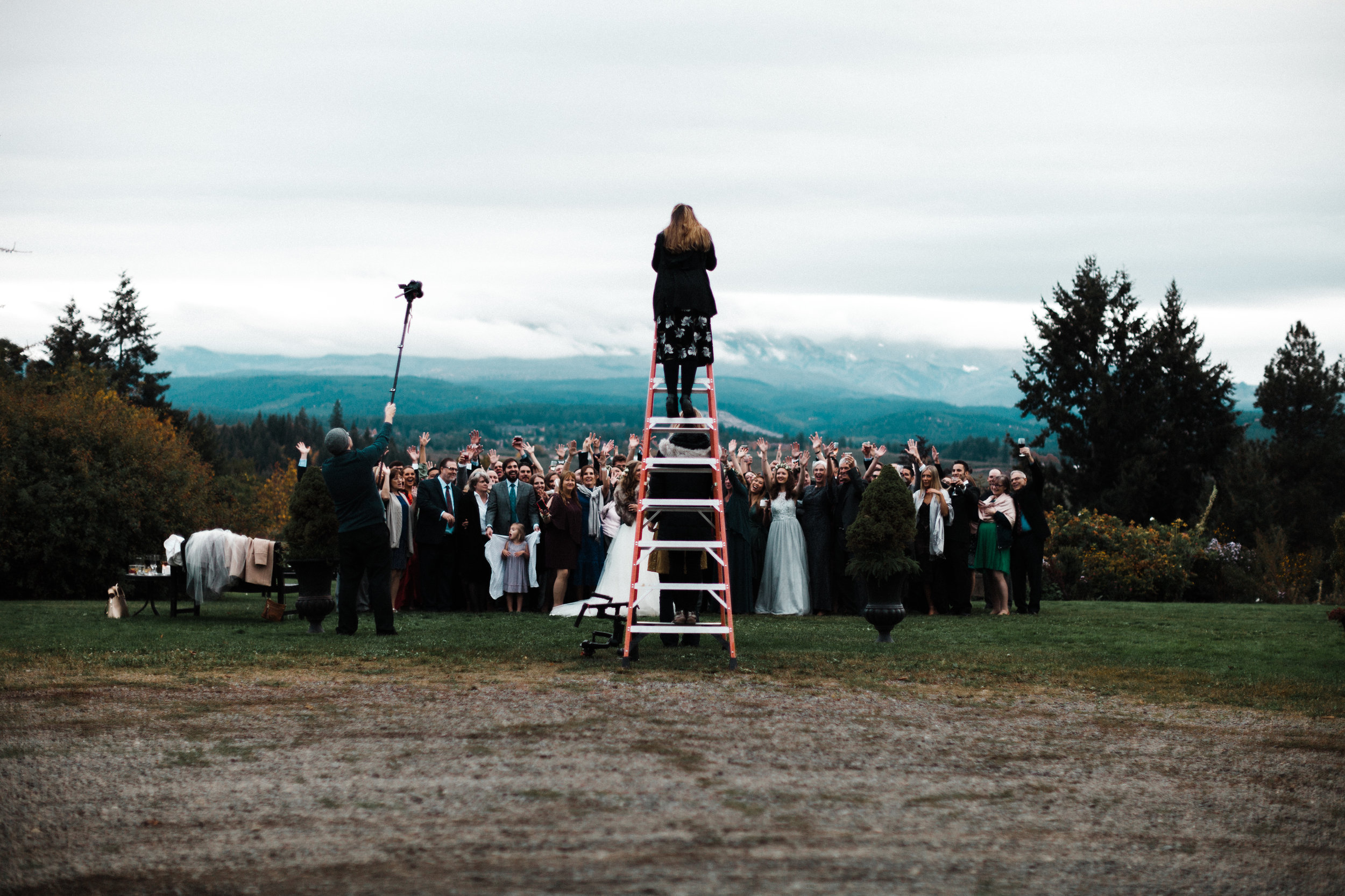 The photographer, (me!) on a ladder, shooting a large group photo at a wedding in Hood River, Oregon.