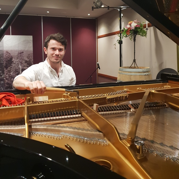 A photo taken by my partner as I put the finishing touches on a Steinway concert grand for a classical music festival.