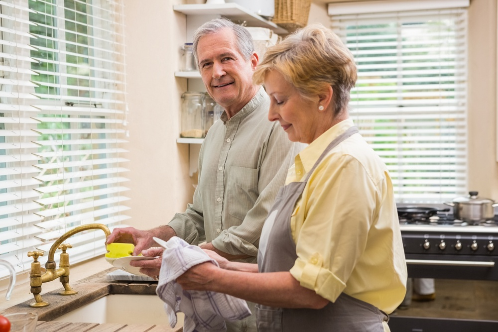 Senior couple washing the dishes at home in the kitchen.jpeg