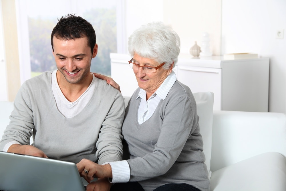 Elderly-woman-with-young-man-using-internet-at-home-min.jpeg