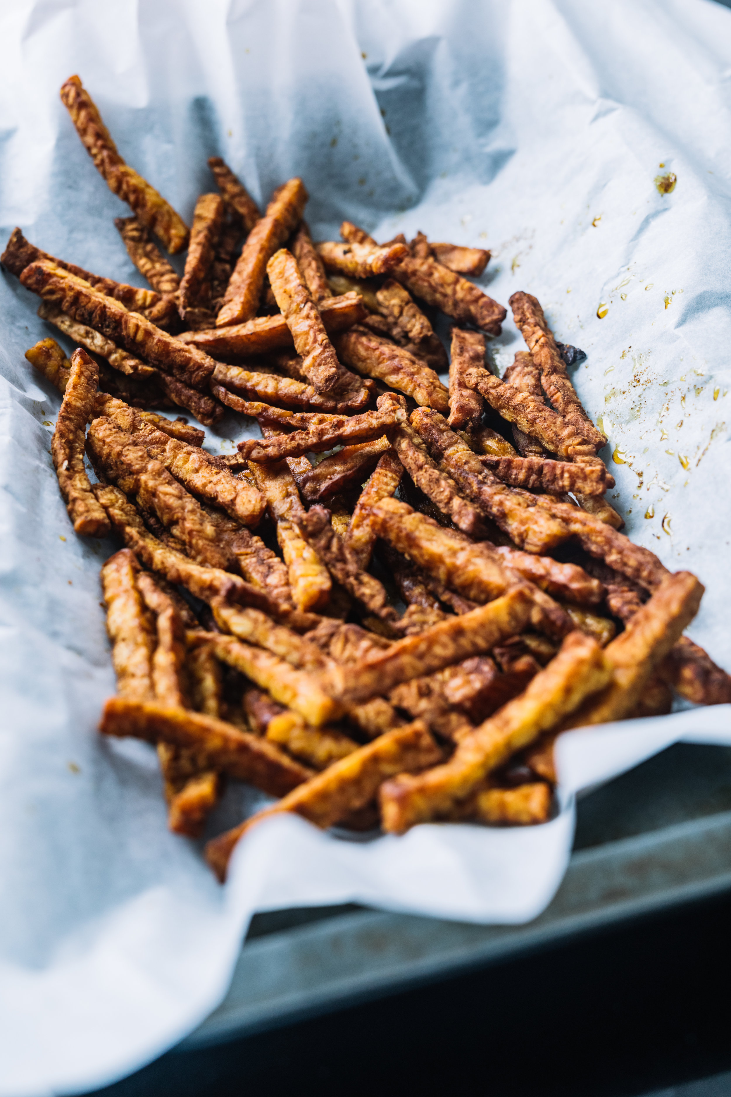 Tempeh Friet - 1 pakje tempeh (250gram)1 EL gerookte paprika poeder (kan ook met gewone)1/2 Theelepel komijn kruiden1/2 Theelepel Kurkumma kruiden1 Theelepen Kerry kruidenZoutPeperZonnebloemolieBakpapierBakplaatZet de oven op 200gradenSnij de tempeh nu in frietjesDoe deze in een kom en voeg de paprika poeder, zout & peper toe. Pan op het vuur met een laagje zonnebloemolie, Bak de tempeh zo'n 5 minuutjes en blijf ze goed door husselen. Leg ze hierna op een bakplaat (met bakpaper) in de oven en geef de tempeh nog 6-8 minuten.