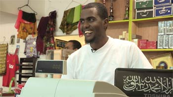 Sayid Hassan standing behind his cash register.