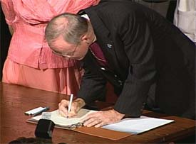 Bishop William Swing signing the URI Charter in 2000.