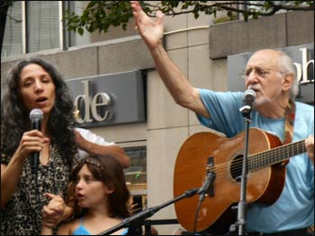 "Peter Yarrow of Peter, Paul, and Mary, standing next to his daughter and granddaughter, sings ""Where Have All the Flowers Gone"" at the early morning rally. – Photo: Ruth Broyde Sharone"