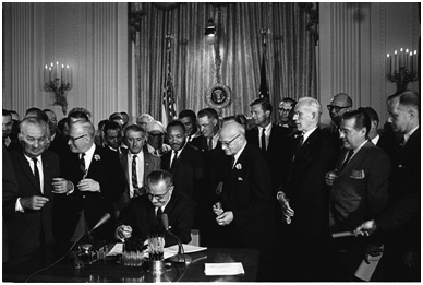 Dr. Martin Luther King Jr. stands behind President Johnson as he signs the landmark Civil Rights Act of 1964. – Photo: Wikipedia, Cecil Stoughton