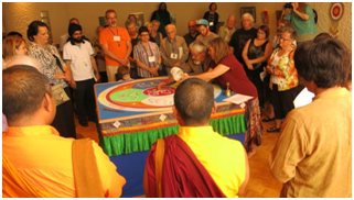 Tibetan Buddhist Lori Petruskevich guides the hands of a local interfaith leader as the dissolution of the beautiful Mandala of Compassion begins at the end of the Connect.