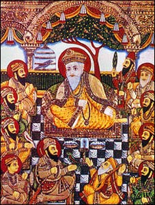 A 19th century painting of Guru Nanak in a circle of the 10 Gurus, with two friends at his feet, the one on the left a Muslim. – Photo: Wikipedia