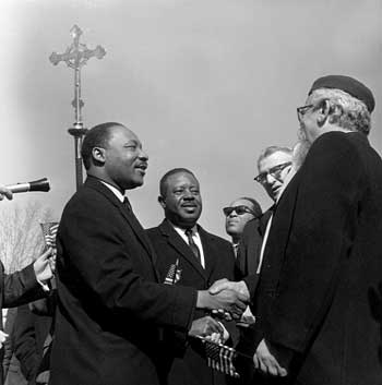 Dr. Martin Luther King, Jr. and Rabbi Abraham Heschel shaking hands at a march. – Photo: thegodface.blogspace.com